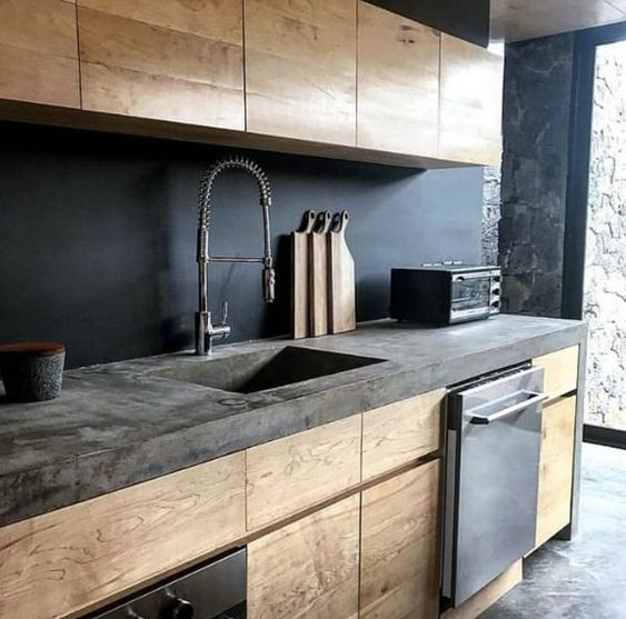 a moody kitchen with sleek wooden cabinets, a chalkboard backsplash and a concrete countertop