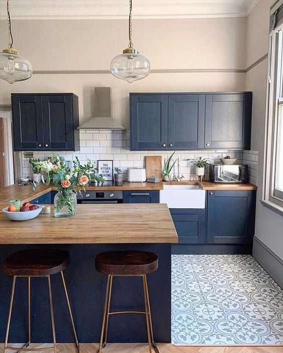 a navy farmhouse kitchen with light stained wooden countertops that soften the look and make it bolder