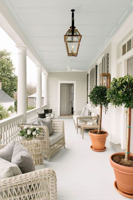 a neutral summer porch with creamy wicker and wooden furniture, potted greenery and comfy chairs in brown