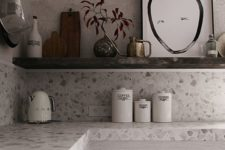 a neutral terrazzo countertop perfectly compliments the whitewashed kitchen cabinets and adds interest