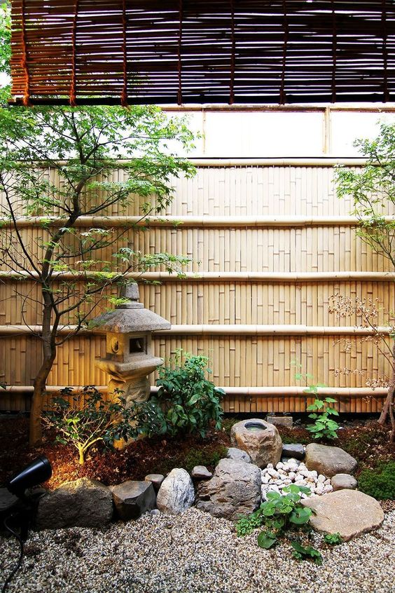 a peaceful Japanese garden with rocks and pebbles, a stone lantern, two trees, greenery and lights is very chic