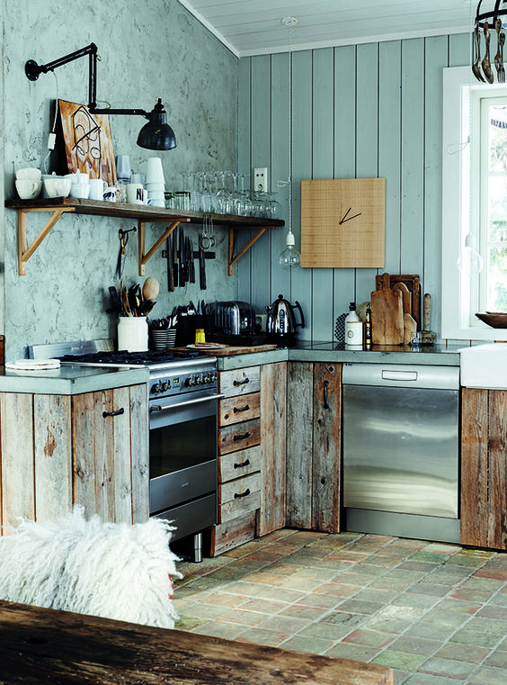 a powder blue chalet kitchen with a plank and plaster wall, reclaimed wooden cabinets and concrete countertops