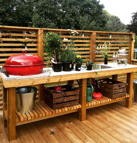 a relaxed rustic bbq zone of wood and concrete, with many potted herbs and a grill plus open storage space