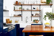 a rich stained wooden countertop and leather stools that highlight it make this bold blue kitchen brighter