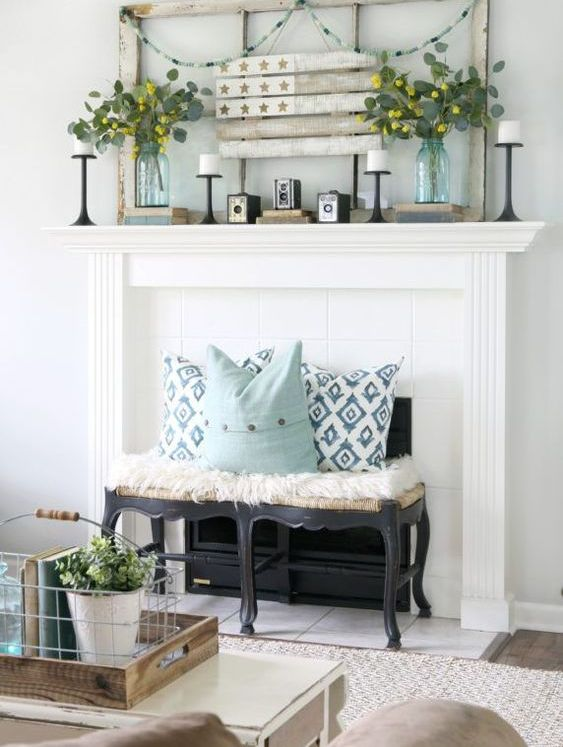 a rustic mantel with a vintage frame and flag, greenery arrangements, candles and vintage books