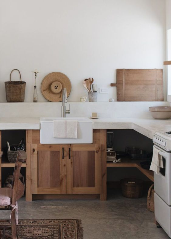 a rustic neutral kitchen with wooden cabinets and open shelves and a white concrete countertop and backsplash