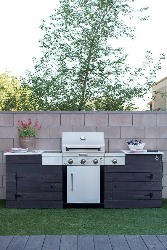 a rustic outdoor bbq area of dark stained wood, with a large grill and some cooking space