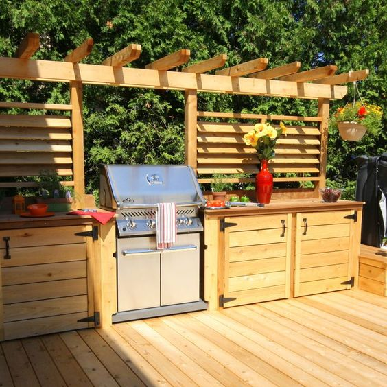 a rustic outdoor bbq area of light stained wood, with much cooking space and a large grill
