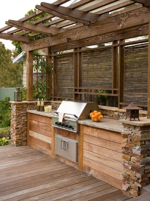 a rustic outdoor bbq zone built of wood and stone, with a cooking countertop and a grill plus lanterns around