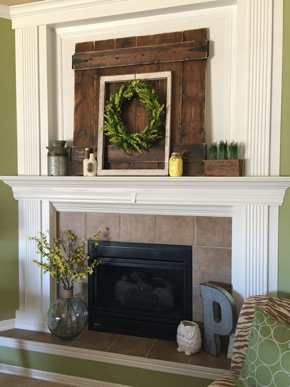 a rustic summer mantel with a greenery wreath, greenery in a planter, a yellow jar, a churn and a pallet wood piece