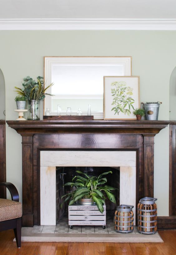 a rustic summer mantel with a vintage artwork, greenery arrangements, crates, bottles and candle lanterns