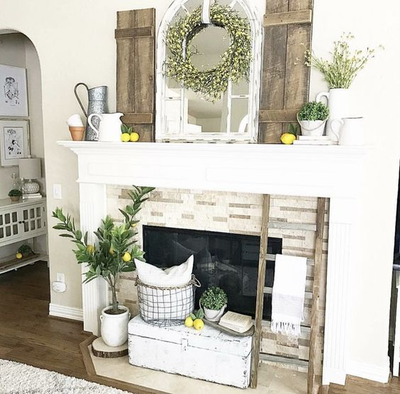 a rustic summer mantel with lemons, greenery, a blooming wreath, shutters, jugs and planters