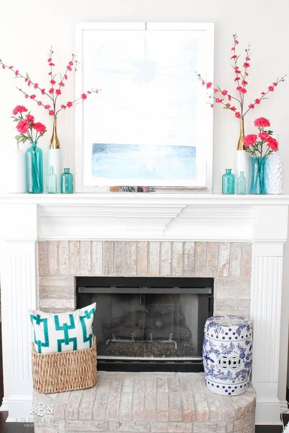 a seaside summer mantel with bright pink blooms, turquoise vases and bottles, a seascape and a basket