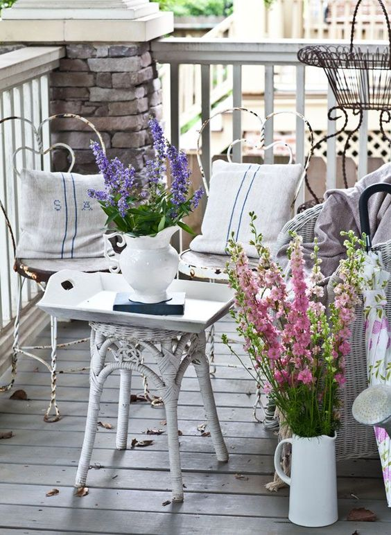 a shabby chic summer porch with metal and wicker furniture and bright floral arrangements