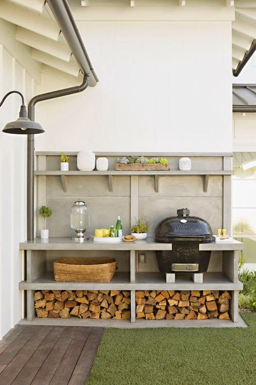 a simple and comfortable outdoor bqq zone with a grill, soem cooking space and firewood stored