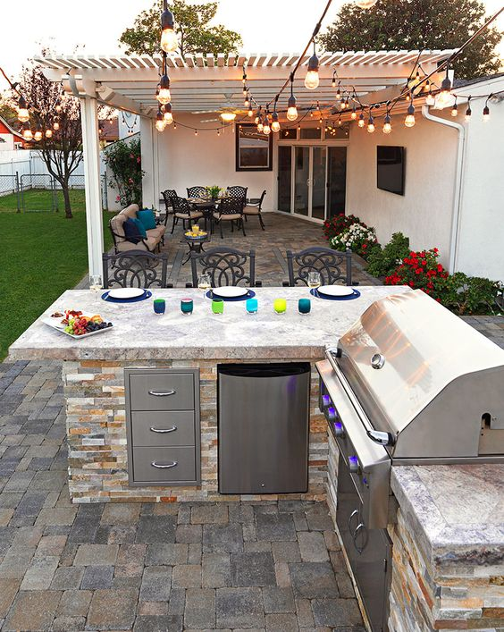 a simple rustic bbq area built of stone, with storage units and a grill plus an eating zone