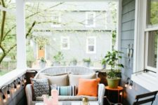 a simple summer porch with a white wicker loveseat, white stools, a wooden chair and some lights around