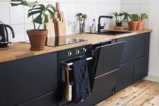 a sleek matte black kitchen with light stained wooden countertops and a white tile backsplash for a contrast