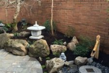 a small Japanese garden with large rocks, a bamboo fountain, pebbles, a stone bowl and trees plus a large stone lantern