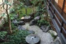 a small Japanese space with a stone bowl, greenery and moss, a bamboo fountain, a low tree and rocks
