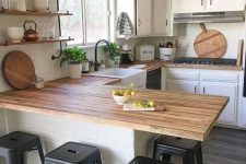 a small and cozy white farmhouse kitchen with light stained butcherblock countertops and black stools for a contrast