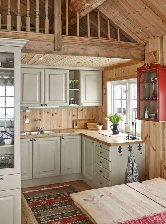 a small rustic chalet kitchen with grey cabinets, wooden countertops, wood plank walls and built-in lights