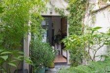 a small townhouse garden clad with stone tiles, potted greenery and living walls plus a built-in bench
