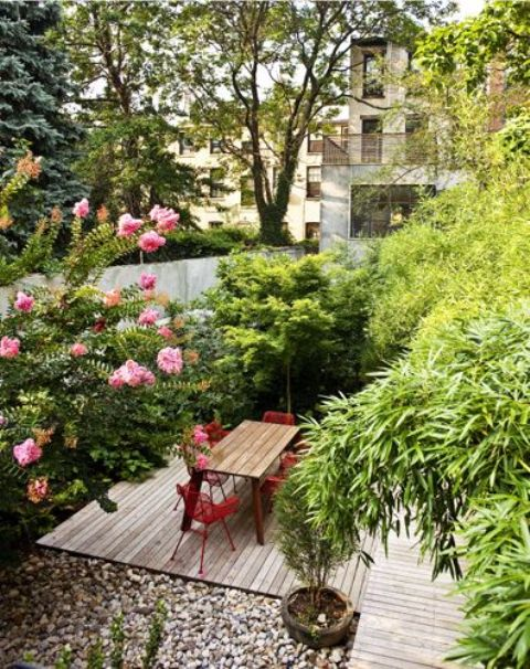 a small townhouse garden with a wooden deck, pebbles, growing greenery and trees plus red chairs and a dining table