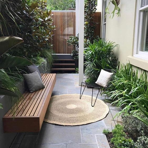 a small townhouse garden with stone tiles, a built-in bench, hairpin leg furniture and potted greenery with much texture