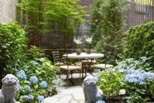 a small townhouse garden with trees, greenery, blue blooms, a contemporary dining set and Asian decor