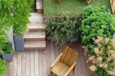 a small townhouse gardne with a wooden deck, a lawn, some potted greenery and wooden furniture