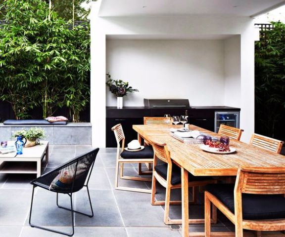 a stylish contemporary dining space done with wooden chairs, a wooden table and blakc upholstery, a black grill next to it