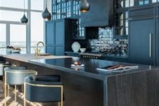 a stylish dark wood kitchen countertop matches the moody kitchen with black glossy tiles and adds chic to the space