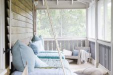 a stylish summer porch with a hanging daybed, a low chair, some neutral and pastel textiles and a boat
