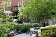 a stylish townhouse garden with a stone platform, a fire pit, a green sofa, planted flowers and greenery