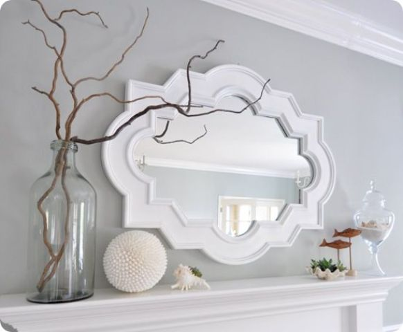 a summer coastal mantel with seashells, greenery, fish figurines, branches and a vintage mirror