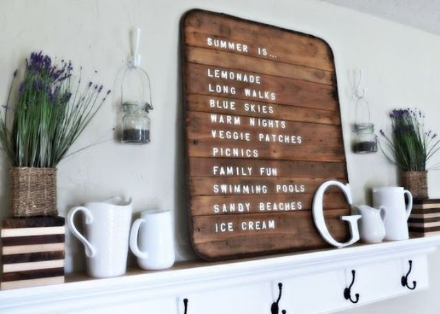 a summer farmhouse mantel with a sign, jugs, lavender, letters and a striped planter
