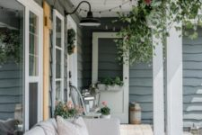a summer farmhouse porch with wicker furniture, potted greenery and blooms, an old door and chair plus potted blooms