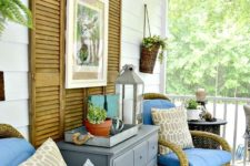 a summer porch with rattan chairs, printed pillows, a grey dresser and shutter decor