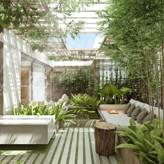 a sunlit inner courtyard with a fireplace and a pond with tropical greenery and a skylight over the space