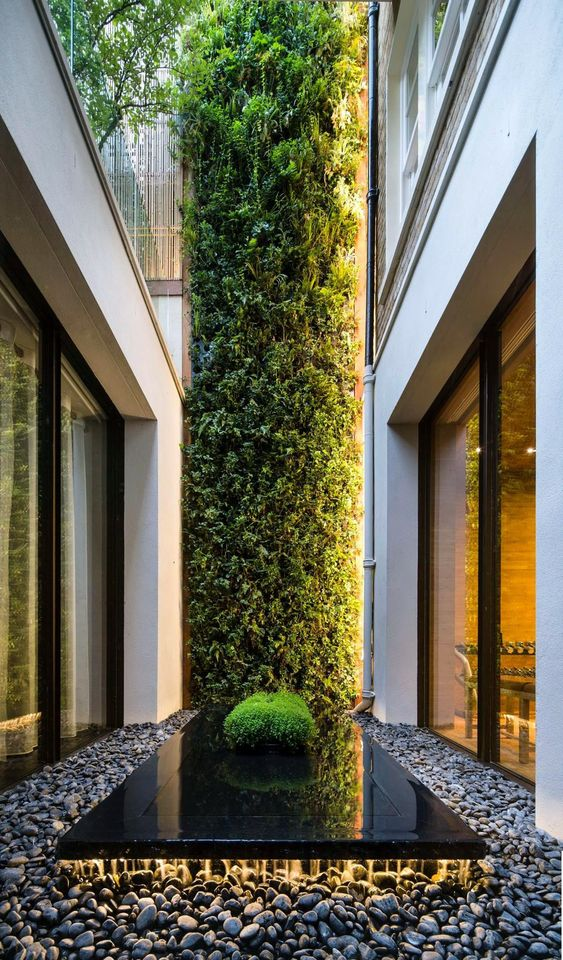 a super chic indoor courtyard with pebbles, a black sleek platform and a greenery wall going up to the top