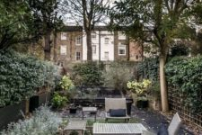 a townhouse garden with a lawn, shrubs and trees, simple wooden furniture and walls around for privacy