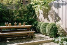 a townhouse garden with stoen steps, greenery and boxwood growing and a simple wooden dining set with benches