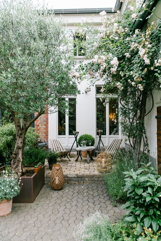 a townhouse garden with stone tiles and bricks, trees, shrubs and greenery, simple wooden furniture and candle lanterns