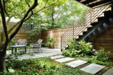 a townhouse garden with stone tiles, potted greenery and trees plus rustic furniture