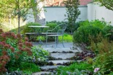a townhouse garden with trees and lush greenery growin even in between the stone steps and metal furniture