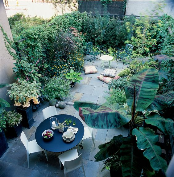a townhouse oasis with stone tiles, a contemporary dining set with a round table, growing greenery and plants and some pillows