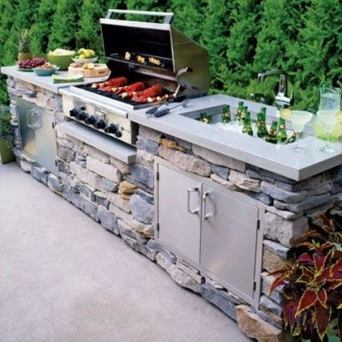 a traditional outdoor bbq area with a stone unit, a concrete countertop, a grill, a cooking zone and a drink cooler