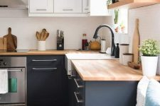 a trendy two tone kitchen in black and white and with light stained butcherblock countertops and matte black faucets