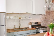 a two tone kitchen with white and dove grey cabinets, light stained butcherblock countertops and gold touches